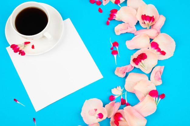 Cup of coffee with flowers decor on light blue table. love and romance concept.