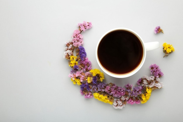 Cup of coffee with flowers on grey surface