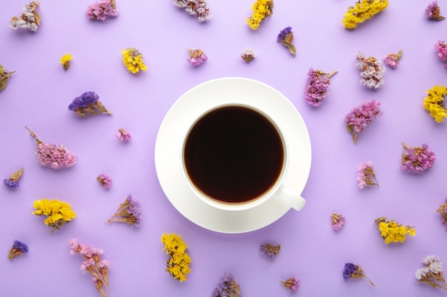Cup of coffee with flowers on purple surface
