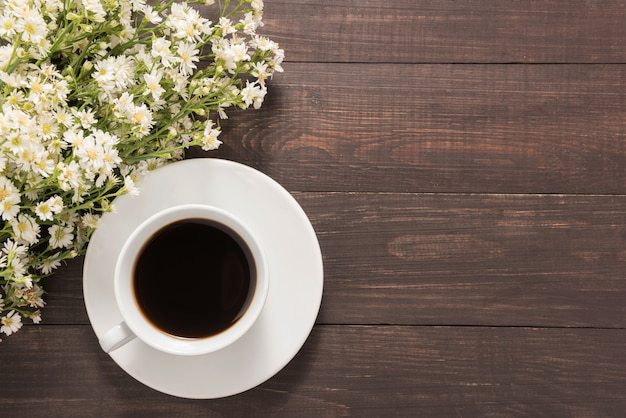 A cup of coffee with flowers on wooden background