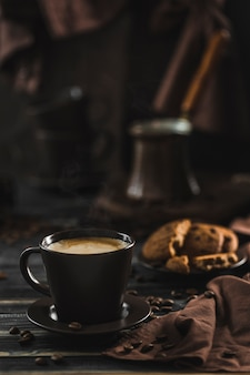 A cup of coffee with foam on a dark wood with oatmeal cookies, scattered grains, coffee maker