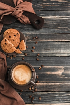 A cup of coffee with foam on a dark wood with oatmeal cookies.