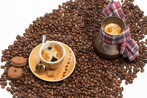 Cup of coffee with froth and turk with coffee with more coffee beans scattered on white background
