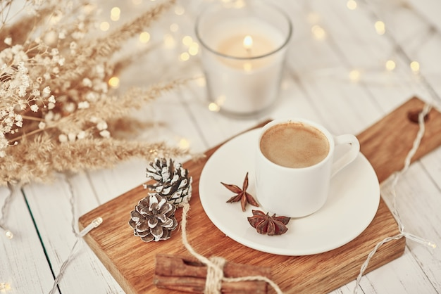 Cup of coffee with garland lights, burning candle and decoration on table. cozy home concept