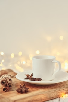 Cup of coffee with garland lights and decoration on table. cozy home concept