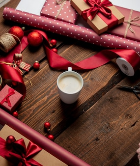 Cup of coffee with gifts and paper on wooden table