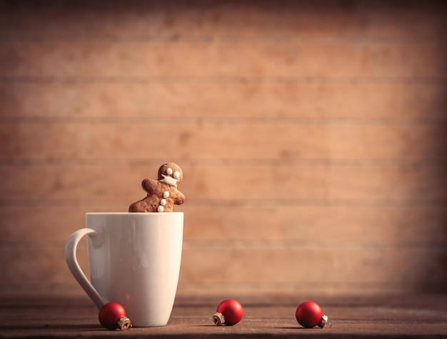 Cup of coffee with gingerbread man and christmas baubles on wooden table