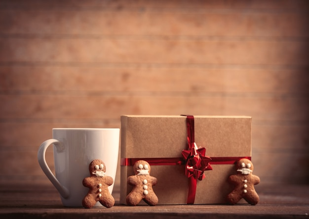 Cup of coffee with gingerbread man and christmas gift on wooden table