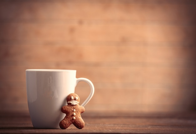 Cup of coffee with gingerbread man on wooden table