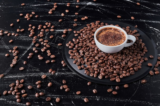 Cup of coffee with grains around.