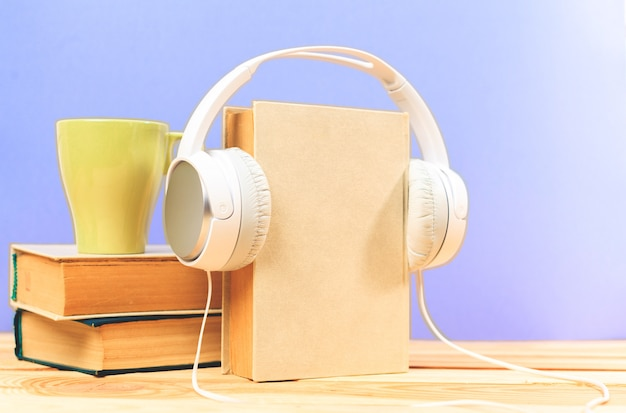 Cup of coffee with headphones on wooden
