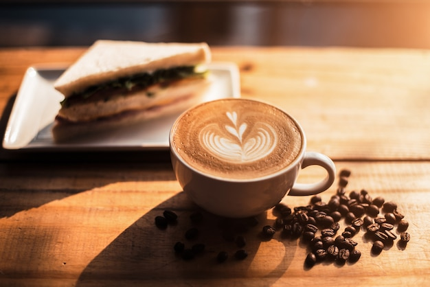 A cup of coffee with heart pattern in a white cup and sandwich on wooden table background