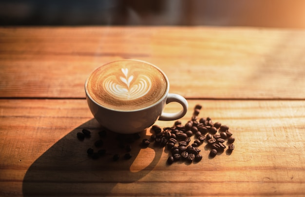 A cup of coffee with heart pattern in a white cup on wooden table background