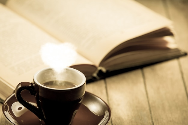 Cup of coffee with heart shape steam and open book on wooden table