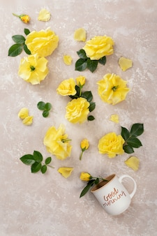 Cup of coffee with the inscription good morning and yellow roses and leaves