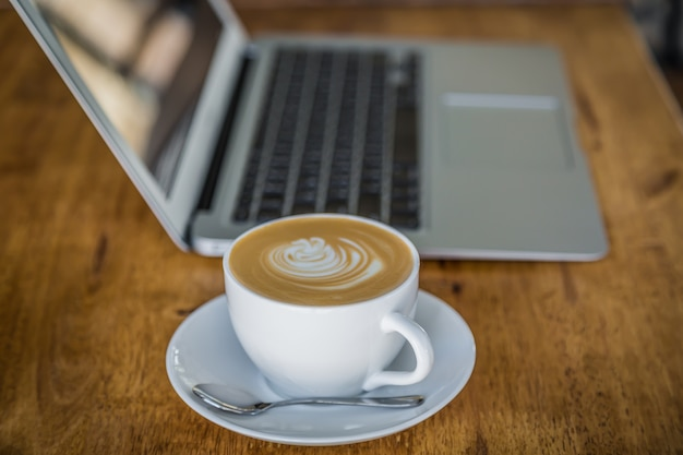 Cup of coffee with a laptop behind