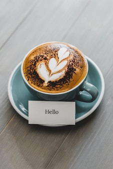 Cup of coffee with latte art and hello greeting text on wood table
