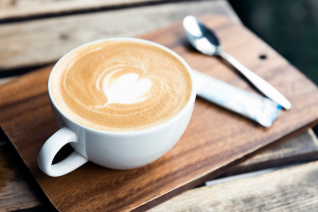 Cup of coffee with latte art on table