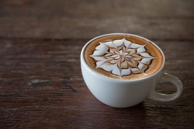 Cup of coffee with  latte art on top with wooden table background
