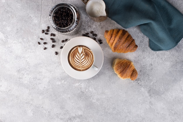 Cup of coffee with latte art. with two delicious croistant duper