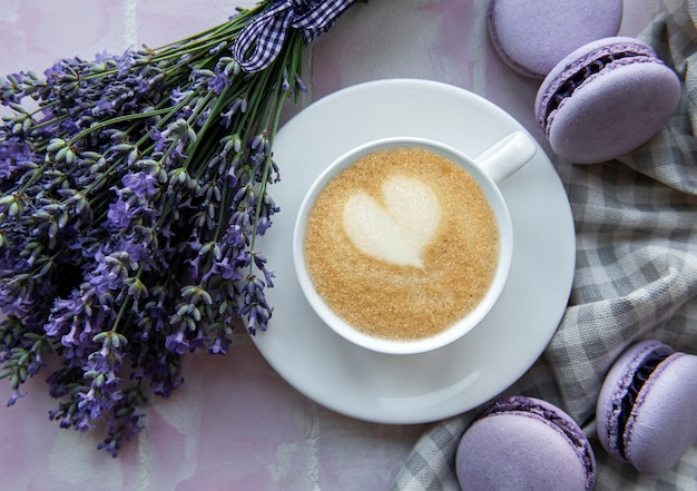 Cup of coffee with lavender-flavored macaroon dessert on pink tiles background