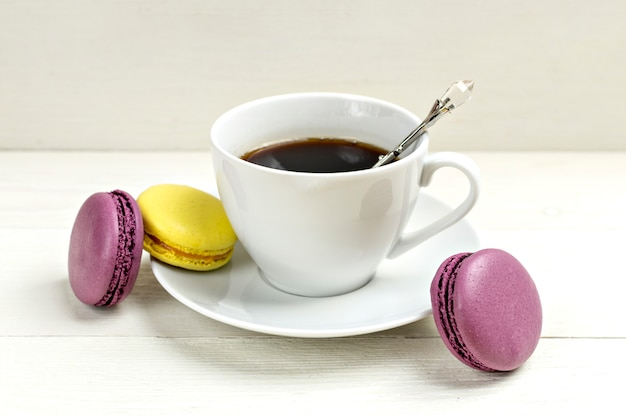 Cup of coffee with macaron on white wooden background. flat lay