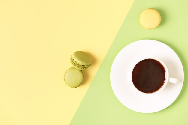 Cup of coffee with macaroons on pastel background