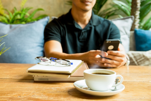 Cup of coffee with man using cell phone and book on table.