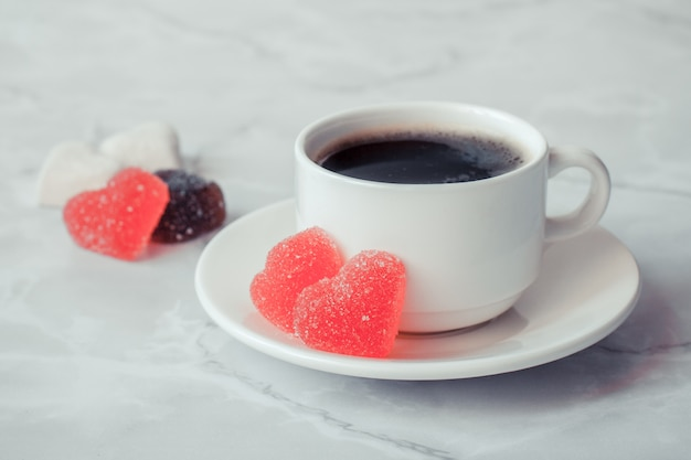 Cup of coffee with marmalade in the shape of a heart on a marble background. copy spase.