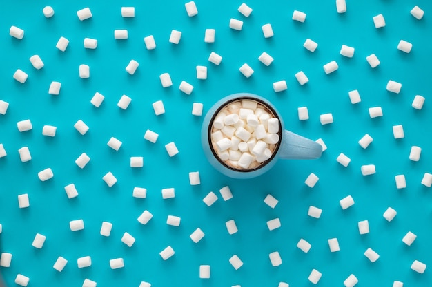 Cup of coffee with marshmallow on blue.