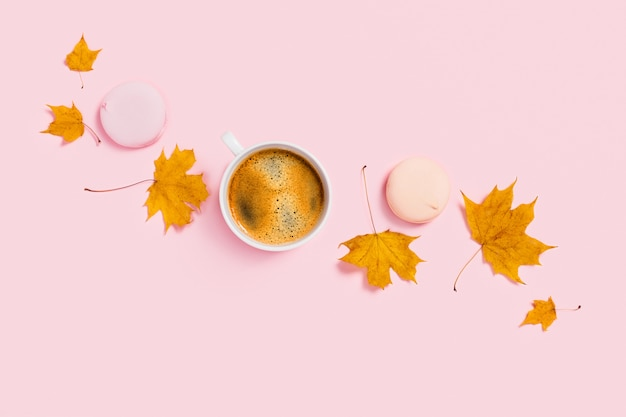 Cup of coffee with marshmallow and maple leaves.