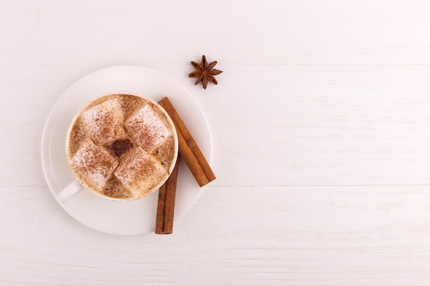 Cup of coffee with marshmallows and cocoa, cinnamon and star anise, on a white background.