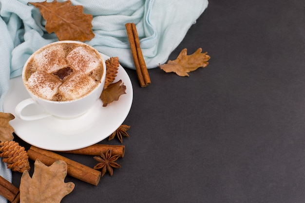 Cup coffee with marshmallows, cocoa, scarf, leaves, dried oranges, spices, on gray background. delicious hot autumn drink, morning mood. copyspace.