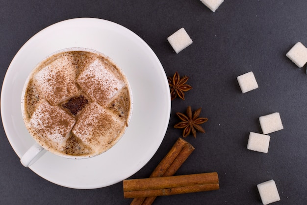 Cup of coffee with marshmallows and cocoa, sugar, cinnamon and star anise, on a gray stone background.