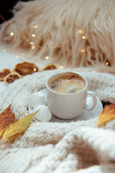 Cup of coffee with meringues, knitted sweater and autumn leaves - autumn concept.