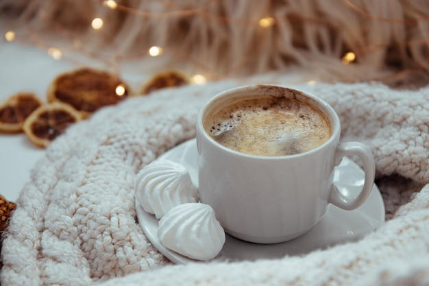 A cup of coffee with meringues and a knitted sweater - the concept of comfort and warmth.