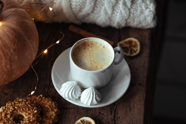 Cup of coffee with meringues, warm cozy photo.