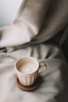 Cup of coffee with milk on beige plaid. flat lay, top view still life morning breakfast. comfort, cosiness and warmth concept. photo in light pastel colors