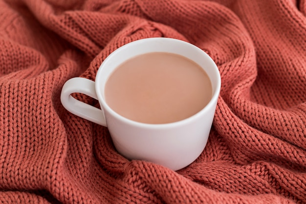 Cup of coffee with milk and chocolate cookies on warm knitted coral blanket.