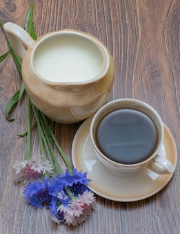 Cup of coffee with milk and cornflowers on wooden table