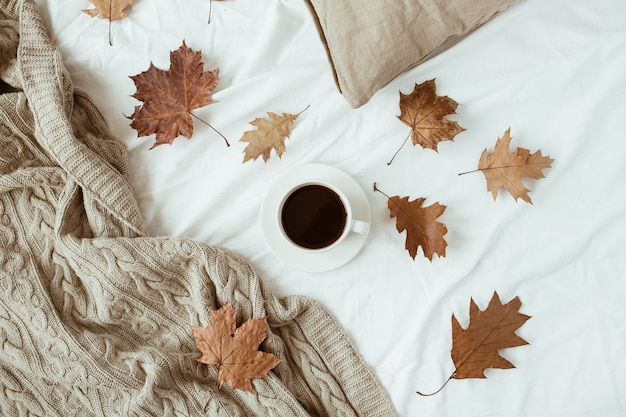 Cup of coffee with milk, dry leaves on bed with white linen, pillow, blanket