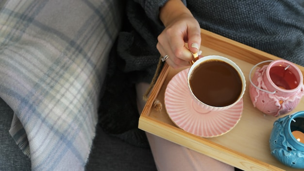 A cup of coffee with milk in female hands on a wooden tray