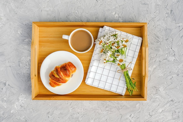 Cup of coffee with milk, freshly baked croissant, checkered napkin and camomile flowers on wooden tray
