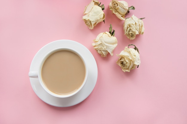 Cup of coffee with milk on pink and dry roses.