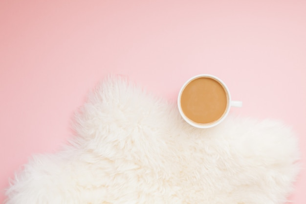 Cup of coffee with milk on pink