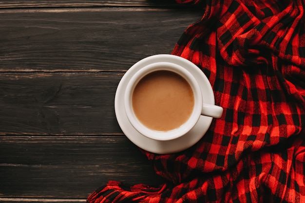 Cup of coffee with milk on wooden table with plaid scarf