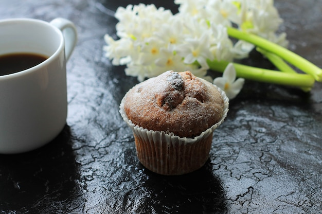 A cup of coffee with a muffin and a hyacinth on wooden background