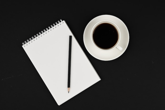 Cup of coffee with notebook and black pencil on black space. business planner