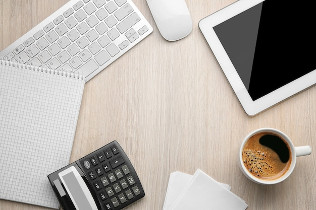 Cup of coffee with office tools on light wooden background