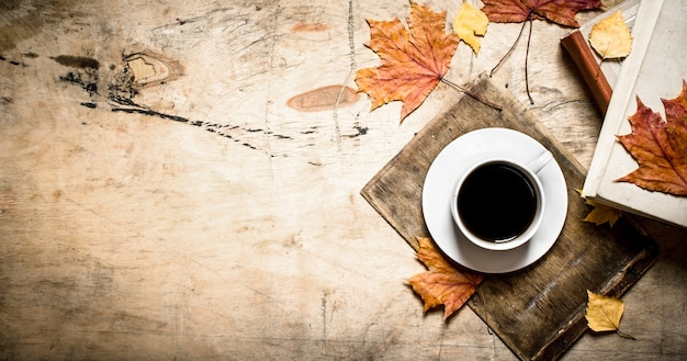 Cup of coffee with an old book and maple leaves. on wooden background.